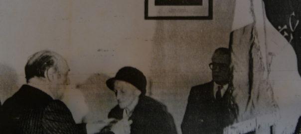 François Mitterrand décore Philomène Mercier en la mairie de Guimaëc, le 28 février 1982. Archives départementales du Finistère: 208 J 126, fonds Alain Le Grand, coupure datée du 3 mars 1982.