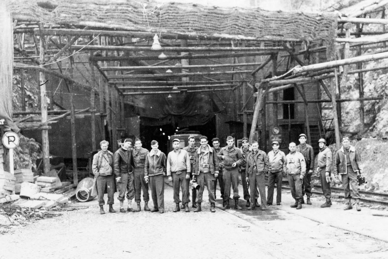 Aviateurs américains devant l'entrée d'une usine de V-1 logée dans un tunnel de Dora, Photographie prise en 1945. Wikicommons.