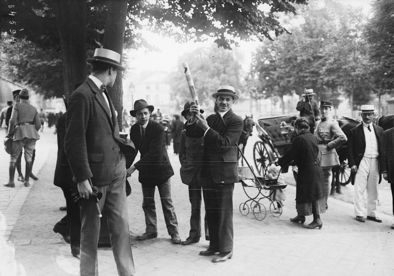 Personnes dans la rue à Versailles dont une brandit un périscope pour observer les manifestations liées à la signature du traité de Versailles le 28 juin 1919. Gallica / Bibliothèque nationale de France: Département Estampes et photographie, Agence Rol, EI-13 (652).