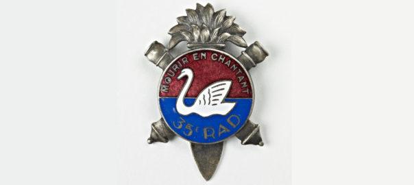 Insigne du 35e RAD. La devise de l'unité est « Mourir en chantant ». Musée de Bretagne : 2010.0035.31.