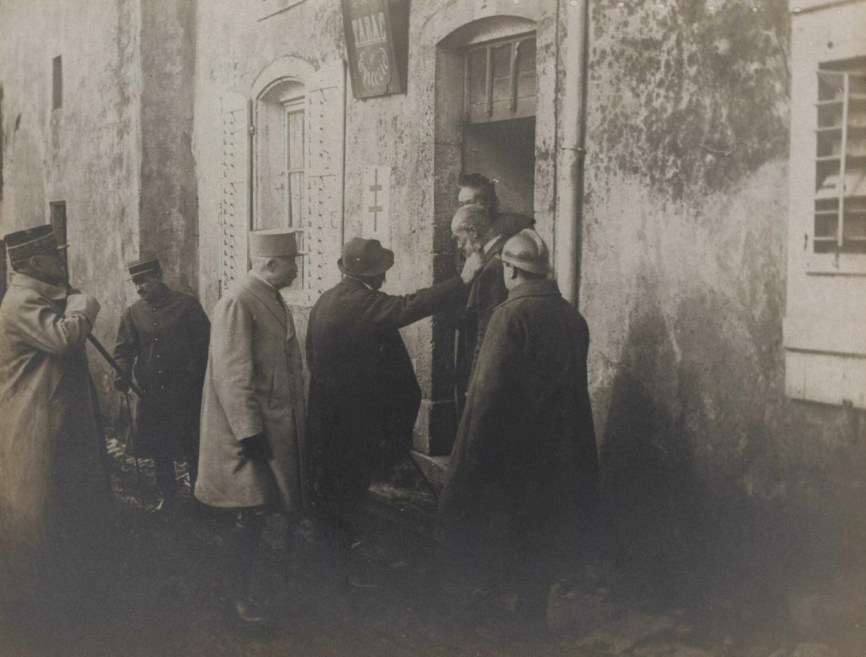 En Lorraine, Georges Clemenceau s'entretient avec un ancien combattant de 1870. Derrière se trouvent les généraux Pétain et Gérard, janvier 1918. La Contemporaine: VAL 168/028.